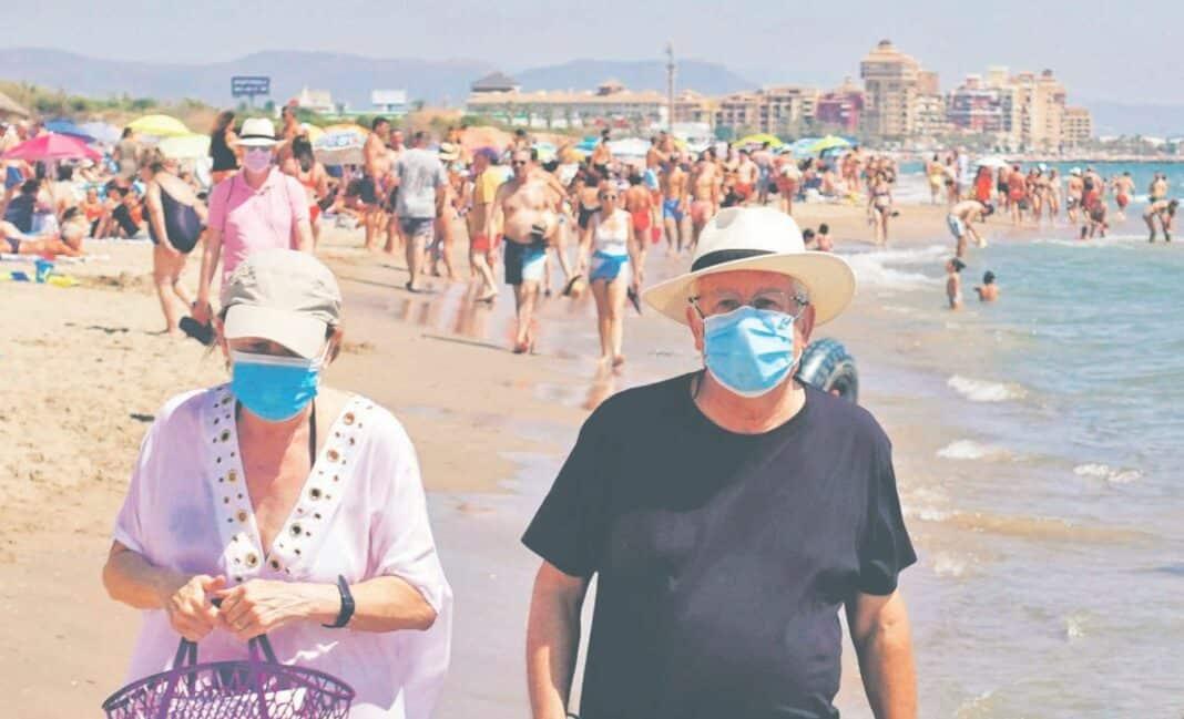 Dwoje ludzi w maseczkach spacerujący po plaży w Hiszpanii